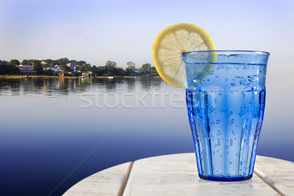 a Blue glass with sparkling water and lemon on a wooden deck overlooking the calm water of a tropica Stock photo © tish1