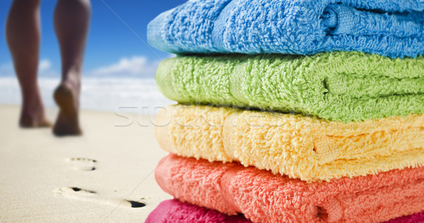 Colorful towels and someone walking on the beach Stock photo © tish1