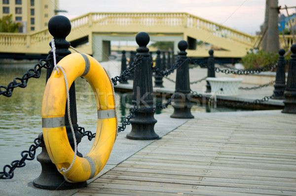 Stock photo: Yellow life buoy on fence