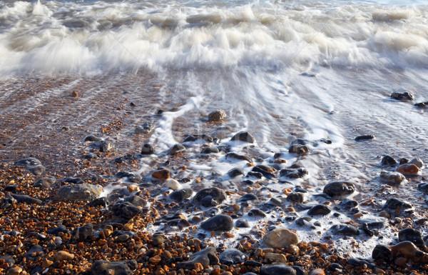 Vague mer caillou plage mousse eau Photo stock © tlorna
