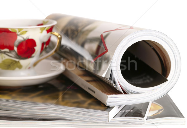 Woman's rolled glossy magazine in stack with tea cup. isolated w Stock photo © tolokonov