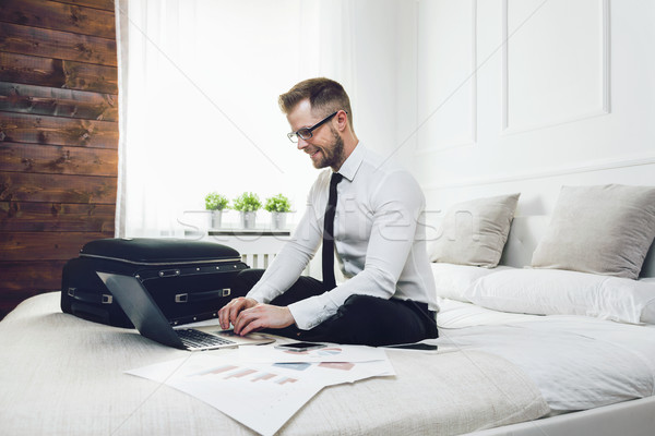 Businessman on bed working with a laptop from his hotel room Stock photo © tommyandone