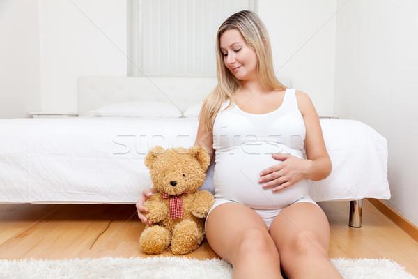 Jonge zwangere vrouw vergadering vloer teddybeer vrouw Stockfoto © tommyandone