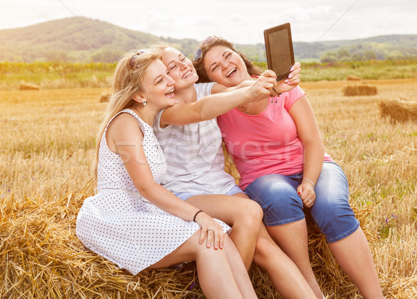 Group of friends in a field taking a picture with a tablet Stock photo © tommyandone