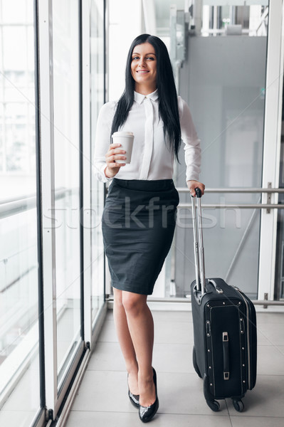 Stock photo: Successful business woman with coffee and suitcase in an office setting