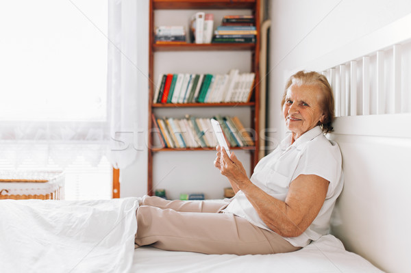 Elderly woman sitting comfortably on bed and using her tablet Stock photo © tommyandone