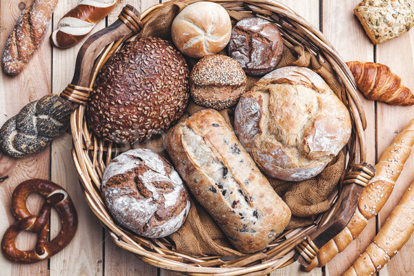 A basket full of delicious fresh bread on wooden background Stock photo © tommyandone
