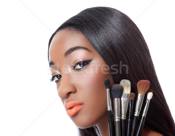 Black woman with straight hair holding makeup brushes Stock photo © tommyandone