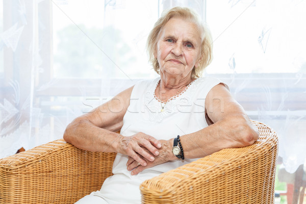 Portrait of an elderly lady sitting in a chair Stock photo © tommyandone