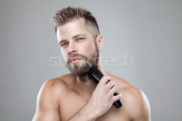 Handsome bearded man trimming his beard with a trimmer Stock photo © tommyandone