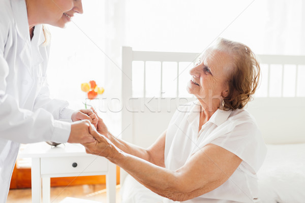 Providing care for elderly. Doctor visiting elderly patient at home.  Stock photo © tommyandone
