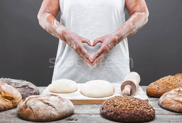 Stock photo: Baker preparing delicious fresh bread and pastry