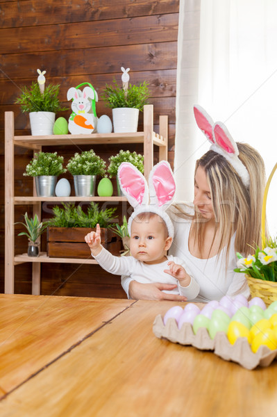 Stock photo: Happy mother and her cute child wearing bunny ears, getting ready for Easter