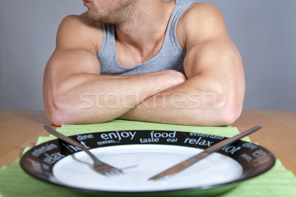 Muscular man with empty plate Stock photo © tommyandone