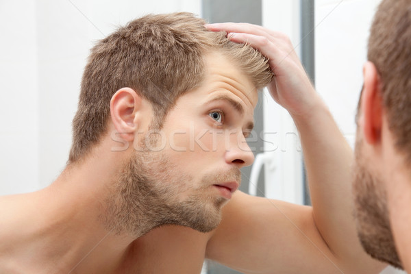 Handsome young man worried about hairloss Stock photo © tommyandone