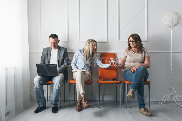 Group of creative people sitting on chairs in waiting room Stock photo © tommyandone