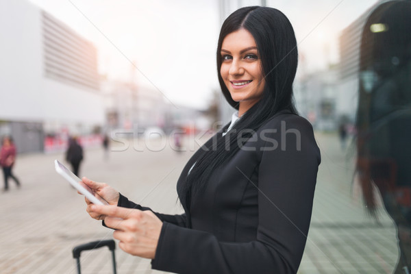 Young business woman with tablet and suitcase in an urban setting Stock photo © tommyandone