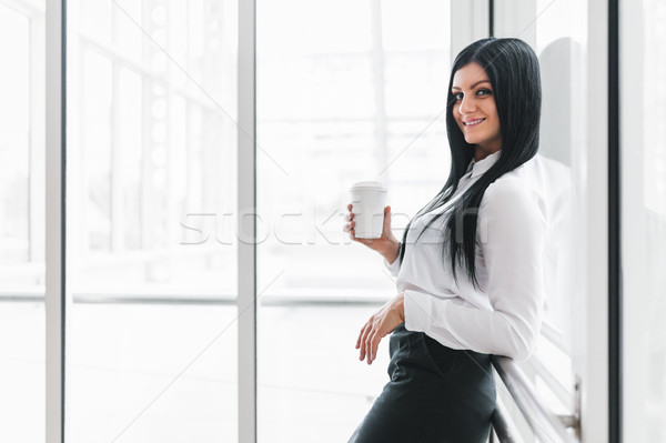 Stock photo: Successful business woman with coffee in an office setting