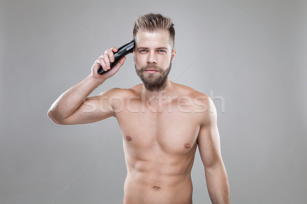 Handsome man cutting his own hair with a clipper Stock photo © tommyandone