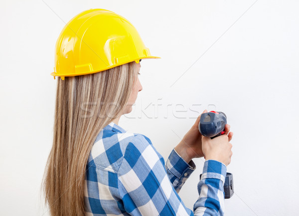 Young woman drilling a hole in the wall  Stock photo © tommyandone