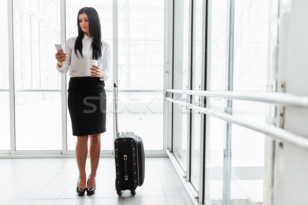 Successful business woman with coffee and suitcase in an office setting Stock photo © tommyandone