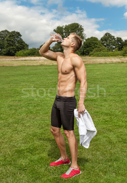 Muscular young man drinking water  Stock photo © tommyandone