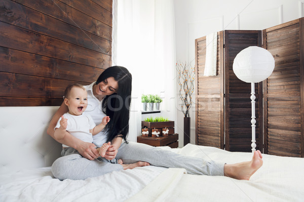 Happy mother with her cute child on the bed having a good time Stock photo © tommyandone