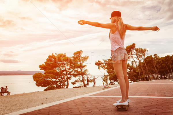 Young carefree woman riding a skateboard along the coast Stock photo © tommyandone