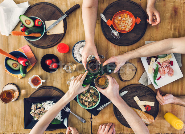 Top view, Group of people sitting at the table with food, enjoying a drink Stock photo © tommyandone