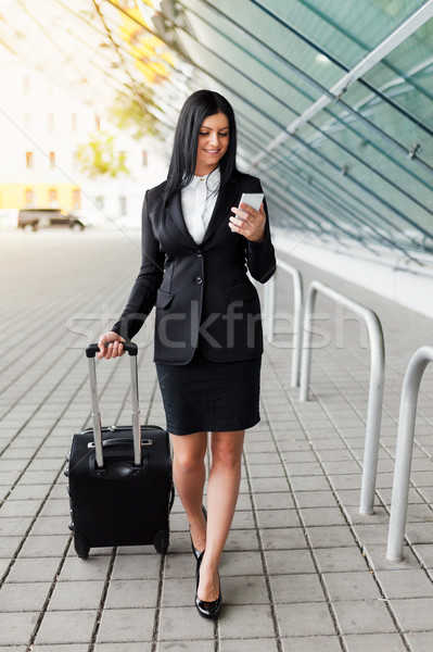 Young business woman with mobile phone and suitcase in urban setting Stock photo © tommyandone