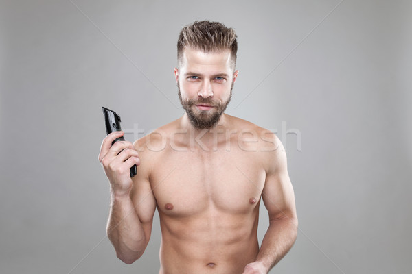 Portrait of young bearded man with a new hair cut, holdin a clipper Stock photo © tommyandone