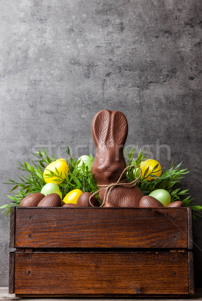 Traditional Easter chocolate bunny and eggs inside a wooden crate Stock photo © tommyandone