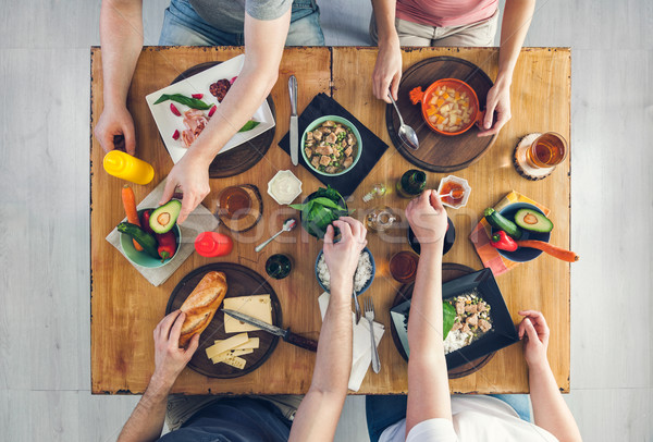 Top view, Group of people sitting at the table having meal Stock photo © tommyandone