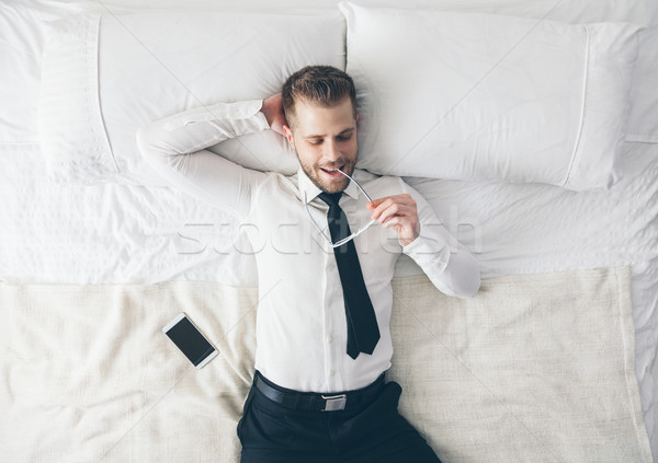 Top view. Handsome businessman with glasses lying on bed Stock photo © tommyandone