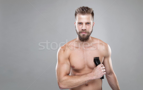 Handsome bearded man with a trimmer shaving off body hair Stock photo © tommyandone