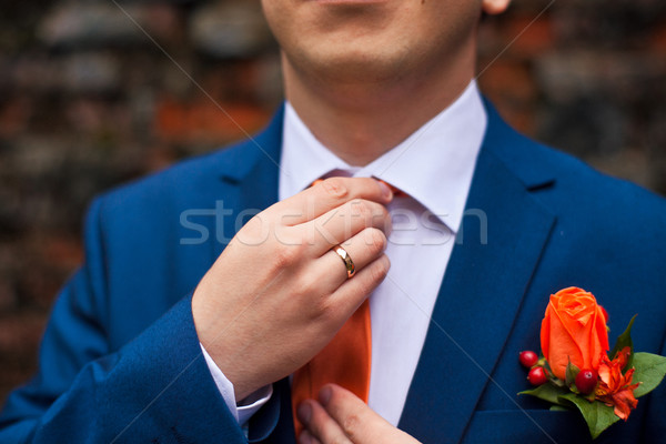 the groom in a blue suit adjusts his orange tie Stock photo © traza