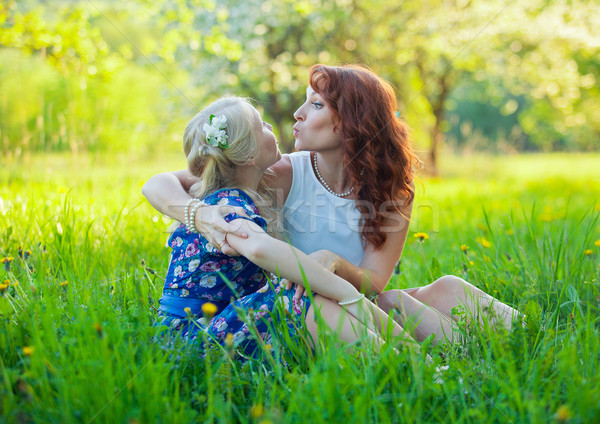 Portrait of happy mother and young daughter with heart in a beautiful blooming fruit garden with whi Stock photo © traza