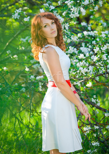 Romantic young woman in the spring garden among apple blossom. Stock photo © traza