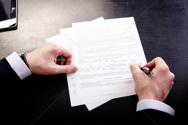 Image of human hand with pen over documents at workplace Stock photo © traza