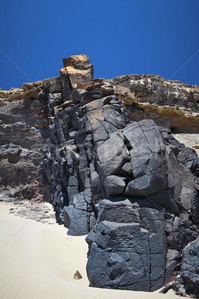 Zwarte rotsen groep blauwe hemel dag strand Stockfoto © trexec