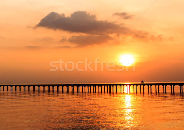 silhouette people driving bicycle on wood bridge with sunset Stock photo © tungphoto