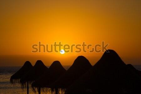 Paille parasol silhouettes orange coucher du soleil tenerife Photo stock © tuulijumala