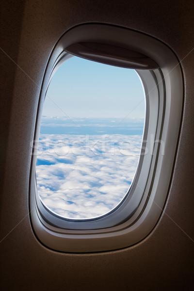 Plane window with blue sky and clouds outside. Stock photo © tuulijumala