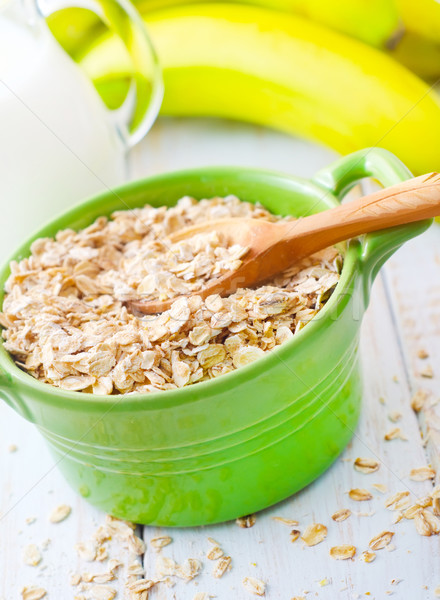 Oat flakes in the green bowl with banana and milk Stock photo © tycoon