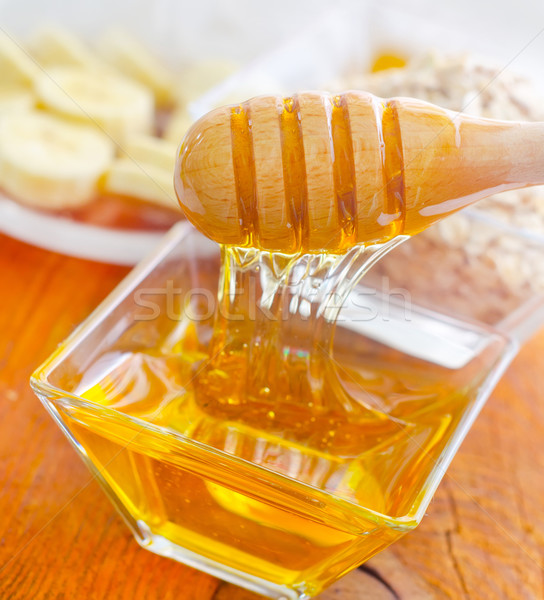 Honey in the glass bowl on the wooden table Stock photo © tycoon