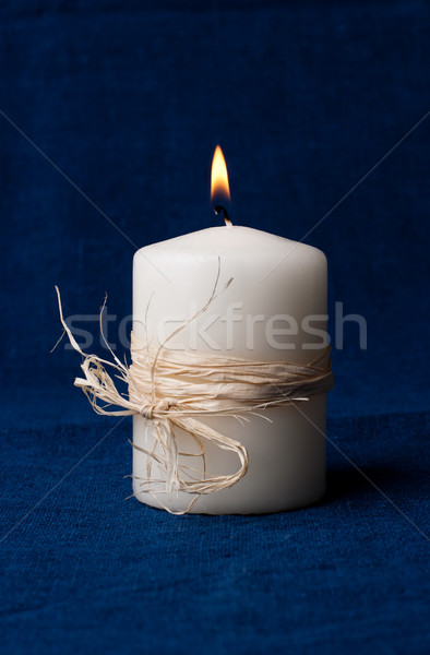 White candle that is lit on a dark blue background Stock photo © ultrapro