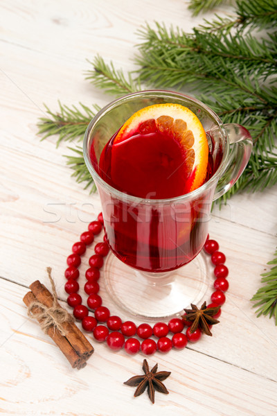 Glass of mulled wine, cinnamon and anise over on white wooden ta Stock photo © user_11056481