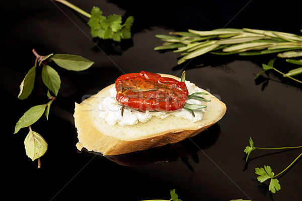 Slice of dried tomato on bread piece on black background Stock photo © user_11056481