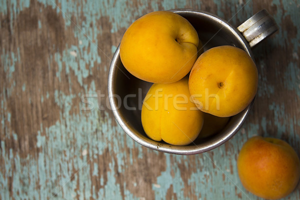 Apricots in  aluminum mug on rustic wooden surface. Stock photo © user_11056481