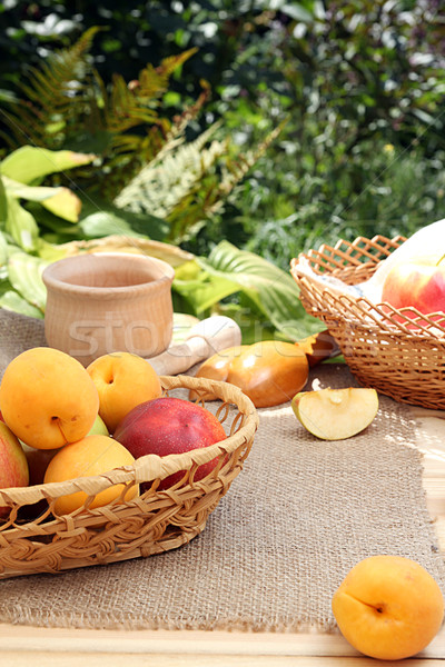 Apricots and apples in wattled basket on sackcloth on a wooden t Stock photo © user_11056481